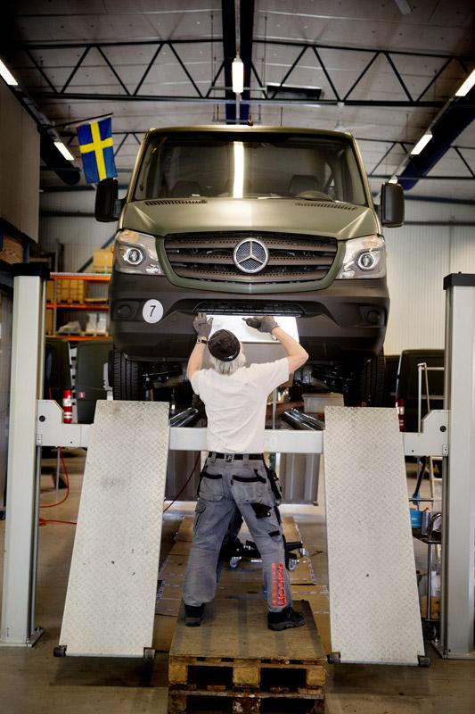 Linus Pettersson arbetar med fronten till en Mercedes-Benz Sprinter.