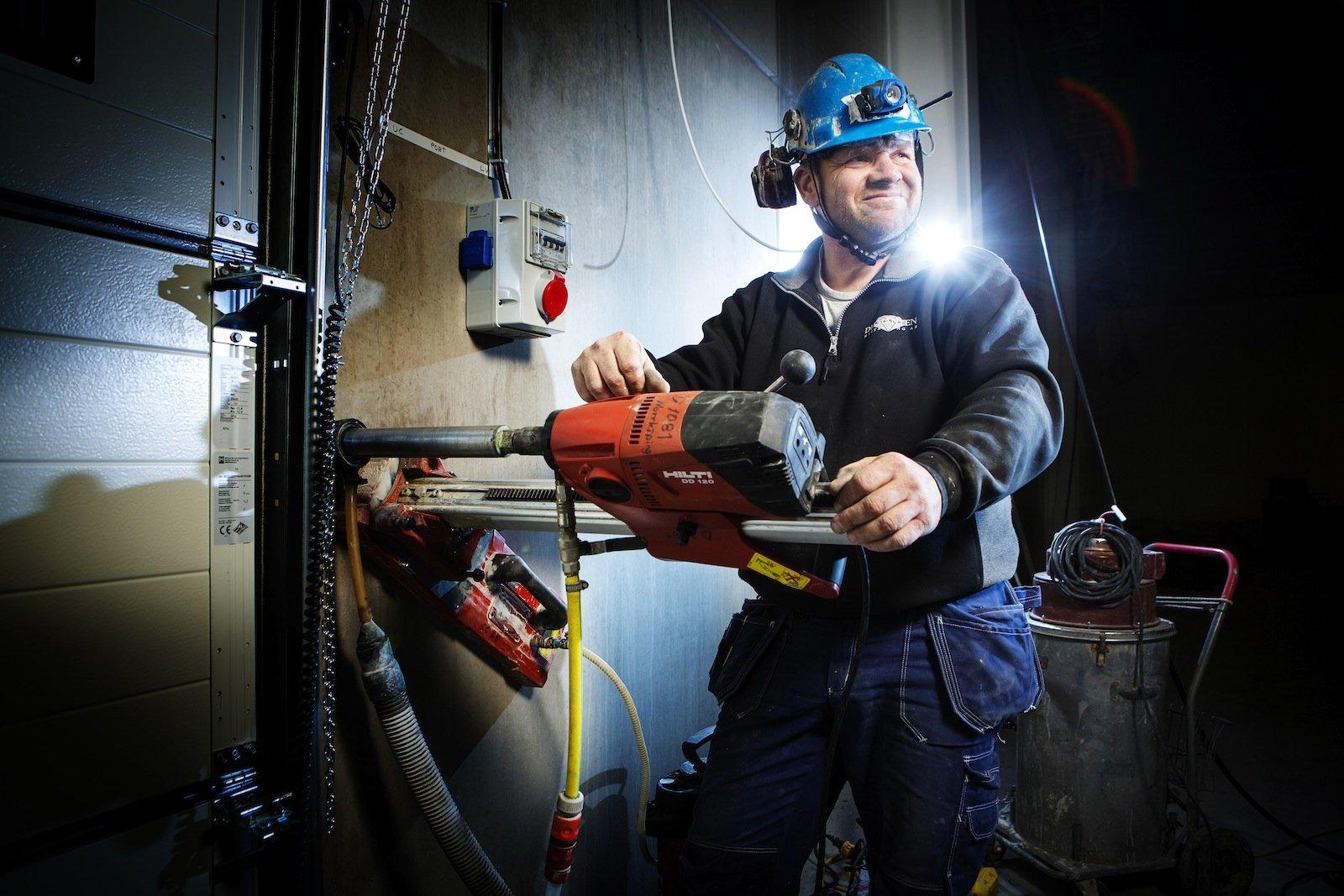 Per-Åke Nilsson från Diamanten AB borrar ett hål i en industrivägg.