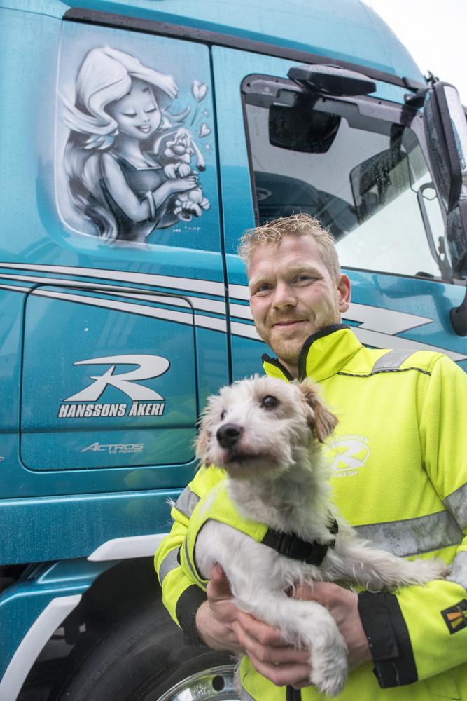 Rasmus Hansson med Sigge, som är hans Jack Russell terrier, med Asterix och Idefix på lastbilen bakom.
